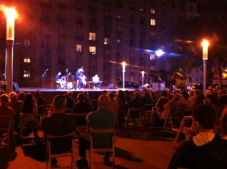 Música a la plaça, públic i veïns escoltant a finestres i balcons